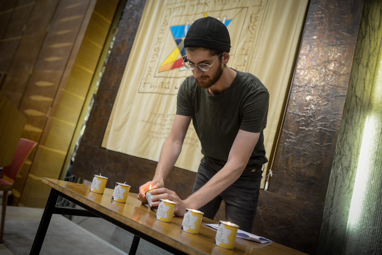 Egy fiú gyertyát gyújt az Adopt a Saphta alapítvány Holokauszt napi megelmékezésén az Ichud Olam zsinagógájában.