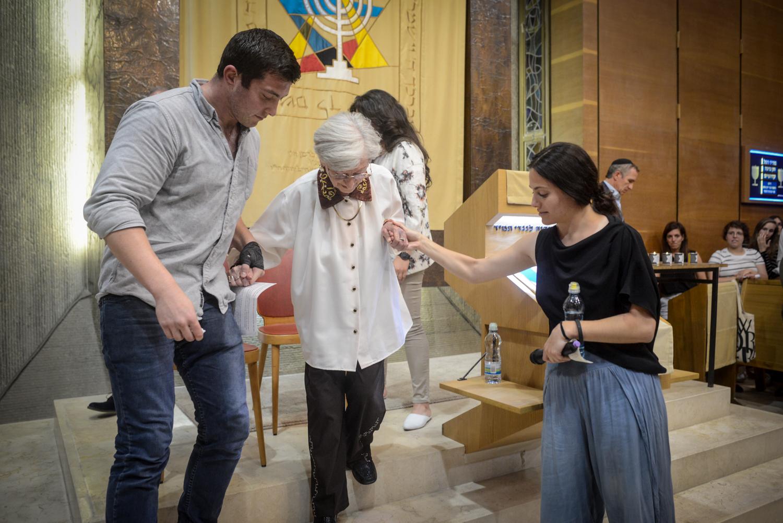 Luba fogja fogadott unokái kezét az Adopt a Saphta alapítvány Holokauszt napi megelmékezésén az Ichud Olam zsinagógájában.
