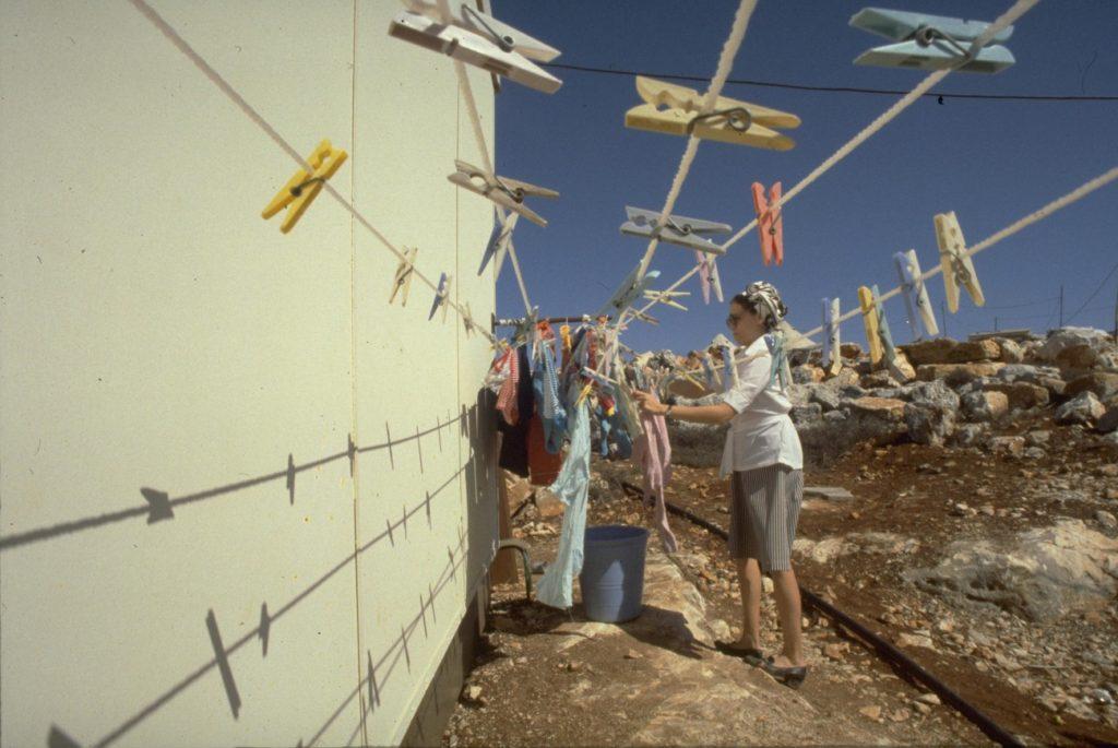 Elon More településen tereget egy telepesnő a karavánja mellett - fotó: Herman Chanania / GPO