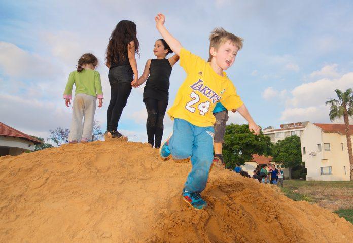 Iskolás gyerekek játszanak egy homokdombon Tel-Avivban - fotó: dnaveh / Shutterstock